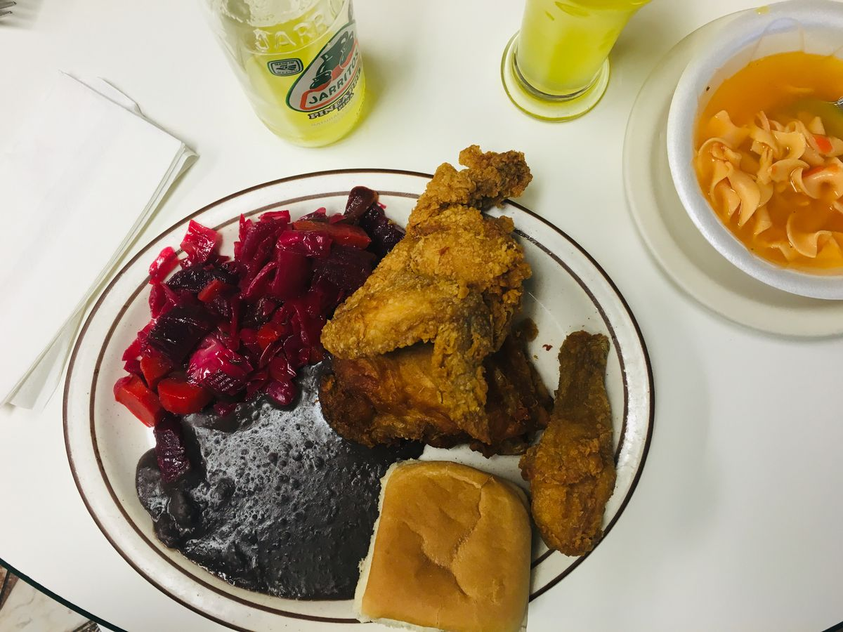 Fried chicken on a plate with black beans, a roll, and purple cabbage slaw.