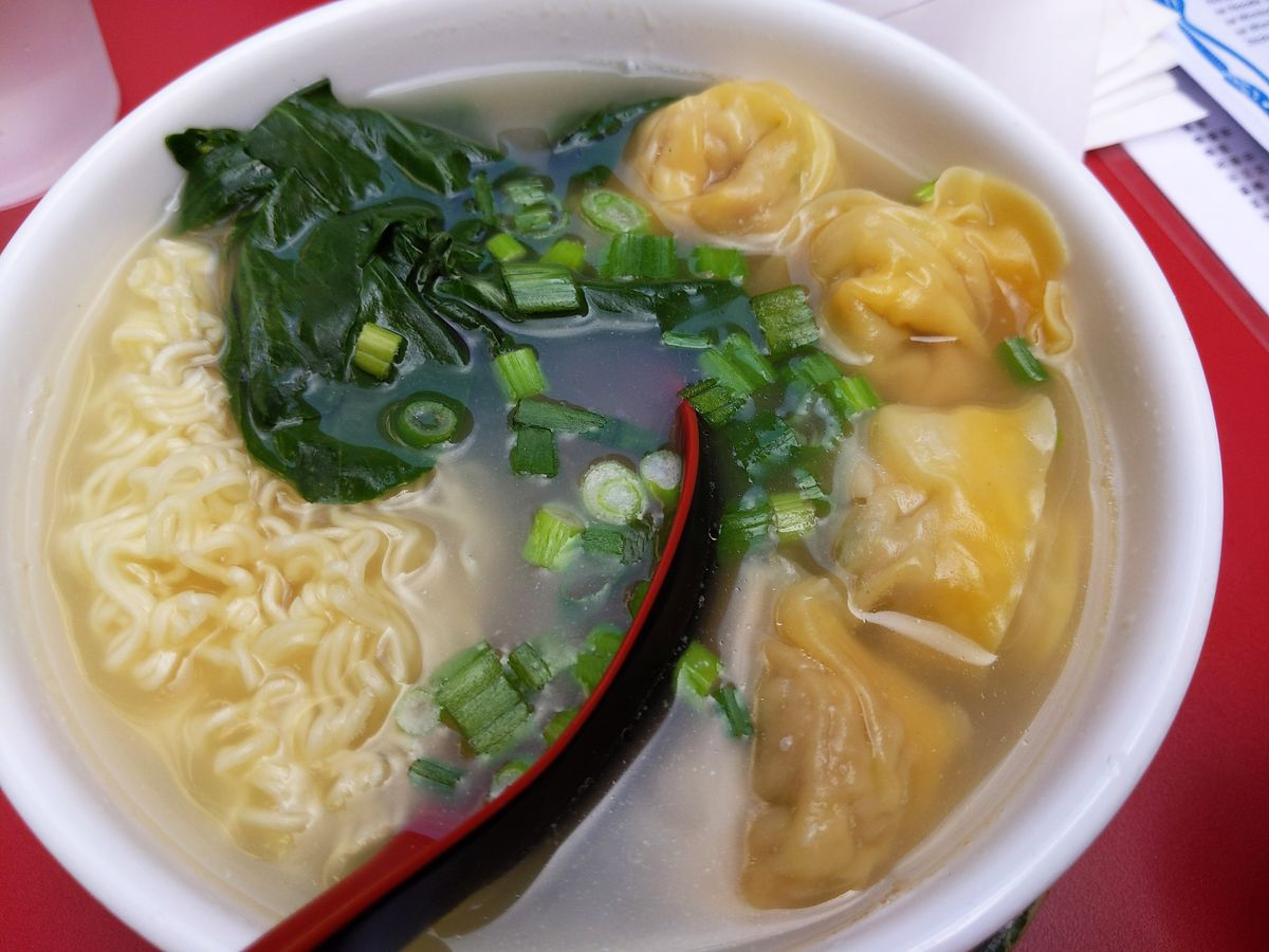A bowl of soup with dumplings greens and yellowish curvy noodles.