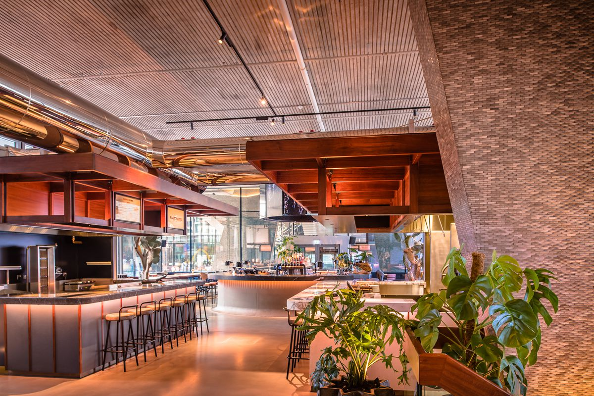 Modern, light-copper coloured interiors, restaurant signage, and plenty of plants inside Arcade Food Theatre at Centre Point in London