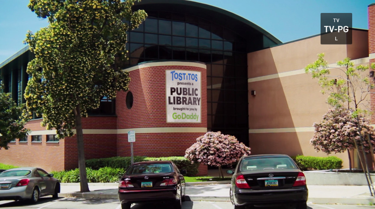 """A building with the sign: """"Tostitos presents a public library brought to you by GoDaddy"""""""