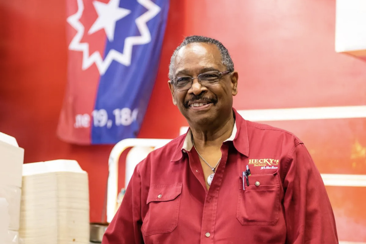 An African-American man in a red shirt, smiling.