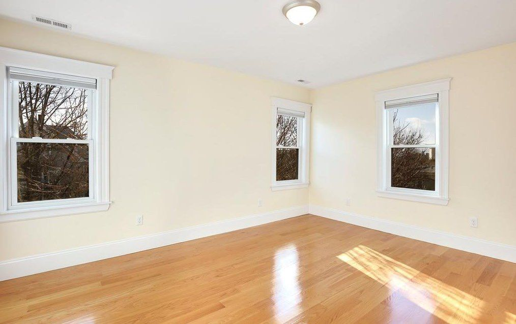 An empty bedroom with windows facing each other.
