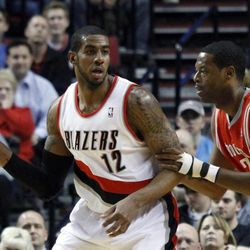 Portland Trail Blazers forward LaMarcus Aldridge, left, looks to pass against Houston Rockets center Marcus Camby during the first quarter of their NBA basketball game in Portland, Ore., Monday, April 9, 2012.
