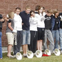 Members of the American Fork High Marching Band comfort one another at the start of the band practice for the funeral of American Fork High band instructor Heather Christensen, who was killed in a bus accident on their way back from a band competition in Idaho over the weekend.