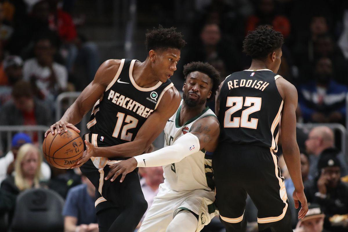 Atlanta Hawks forward De'Andre Hunter controls the ball against Milwaukee Bucks guard Wesley Matthews in the second half at State Farm Arena.