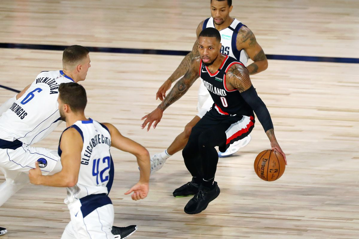 Damian Lillard of the Portland Trail Blazers controls the ball against Kristaps Porzingis #6 and Trey Burke #32 of the Dallas Mavericks during the first half at The Field House at ESPN Wide World Of Sports Complex on August 11, 2020 in Lake Buena Vista, Florida.