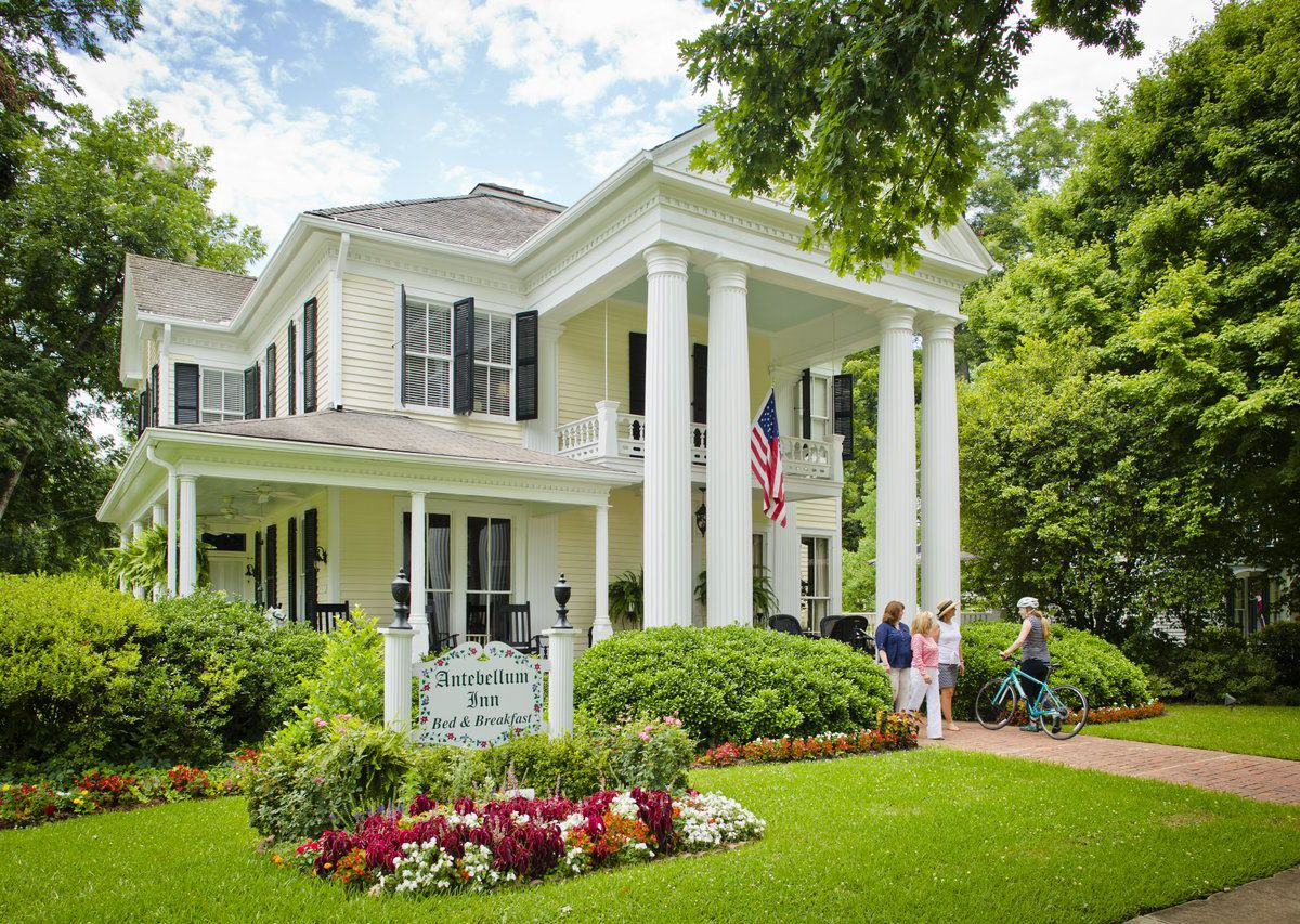 The exterior of an inn. There are columns and multiple stories. There is a sign in front of the inn that reads: Antebellum Inn. There is a lawn, flowers, and trees surrounding the inn.