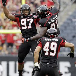 Northern Illinois defensive end Joe Windsor (97) celebrates with defensive tackle Anthony Wells (91) and defensive end Jason Meehan (49) after Windsor sacked Iowa quarterback James Vandenberg (16) during the first half of an NCAA college football game at Soldier Field in Chicago, Saturday, Sept. 1, 2012.