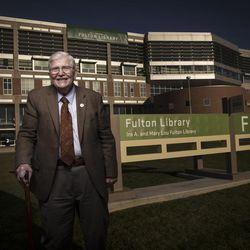 """Ira A. Fulton poses in front of the UVU library, which was renamed as the Ira A. and Mary Lou Fulton Library as part of the unveiling of the """"Roots of Knowledge"""" on the UVU campus in Orem on Friday, Nov. 18, 2016."""