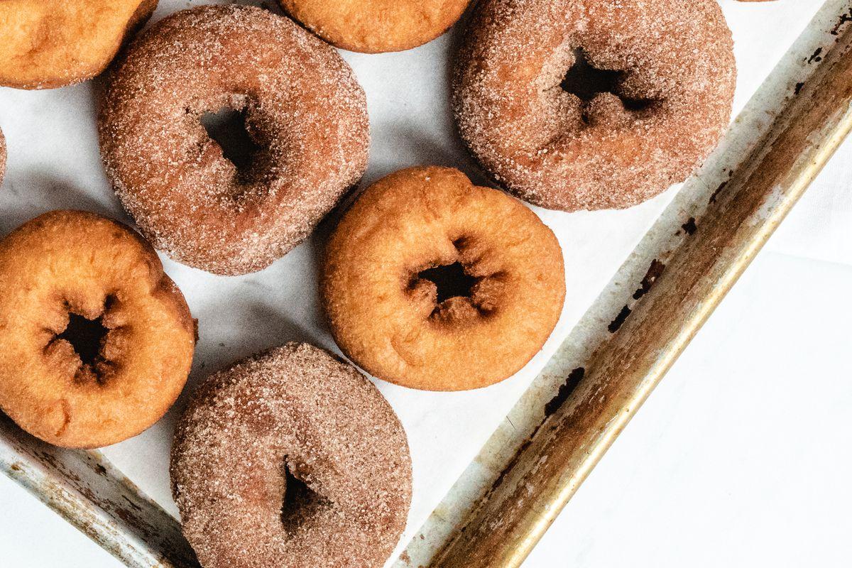 Cinnamon sugar and plane cider doughnuts on a baking tray.
