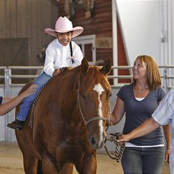 Hope Rowley rides while Valerie Duffin, left, and Andrea Smith help and Cindy Becker leads, at the Buffalo Ranch in Farmington on Thursday. The therapeutic riding is organized by the nonprofit group Therapeutic Assets.