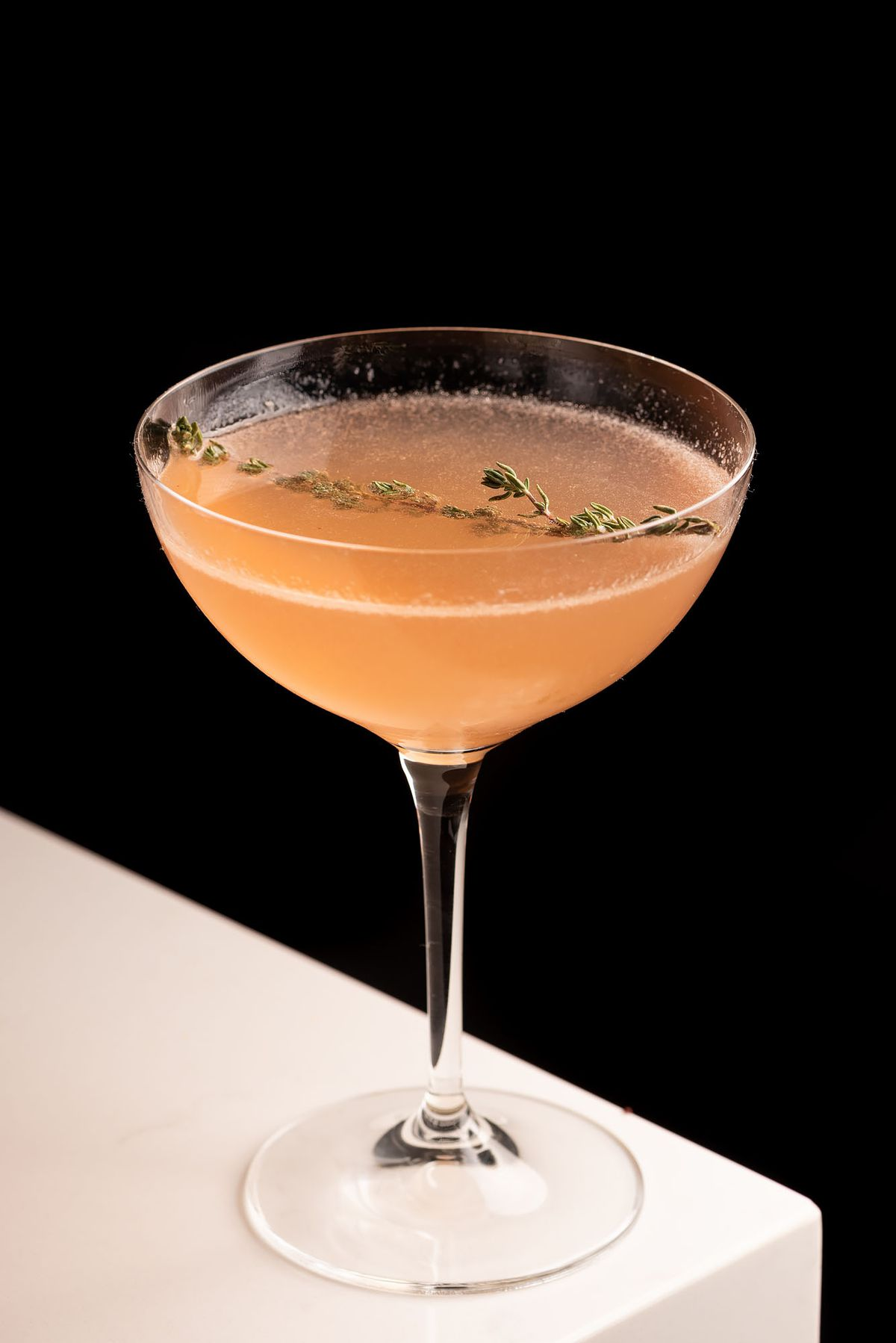 A light pink cocktail with a sprig of thyme.