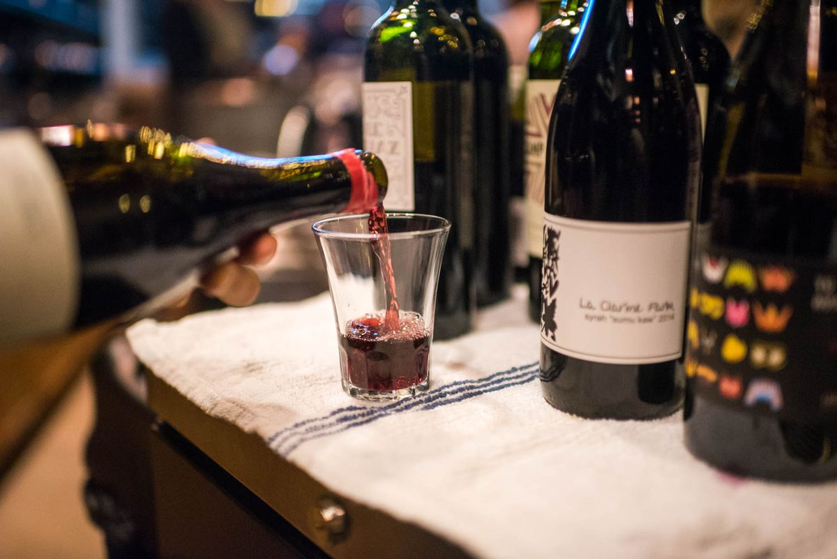 A bottle of red wine is poured into a glass tumbler on a table holding additional wine bottles