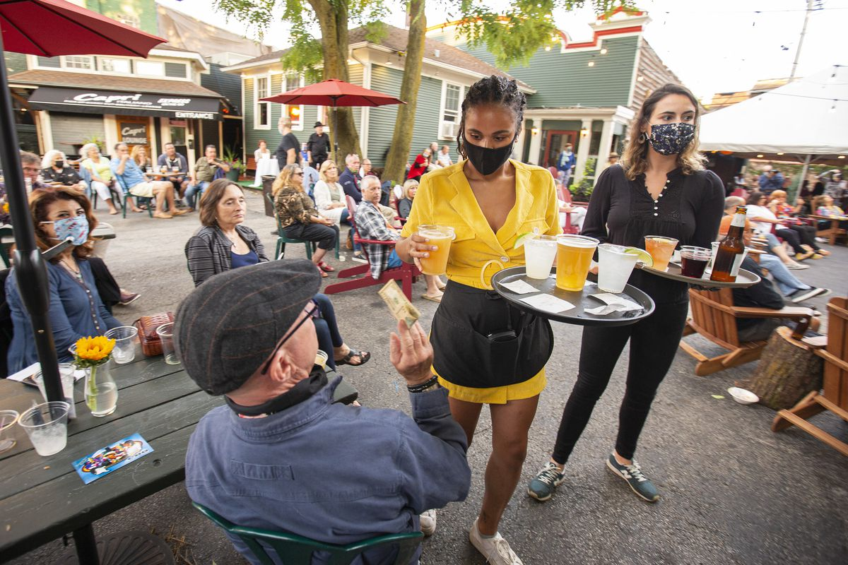 A server in a yellow dress hands and black mask hands a beer to a seated customer.