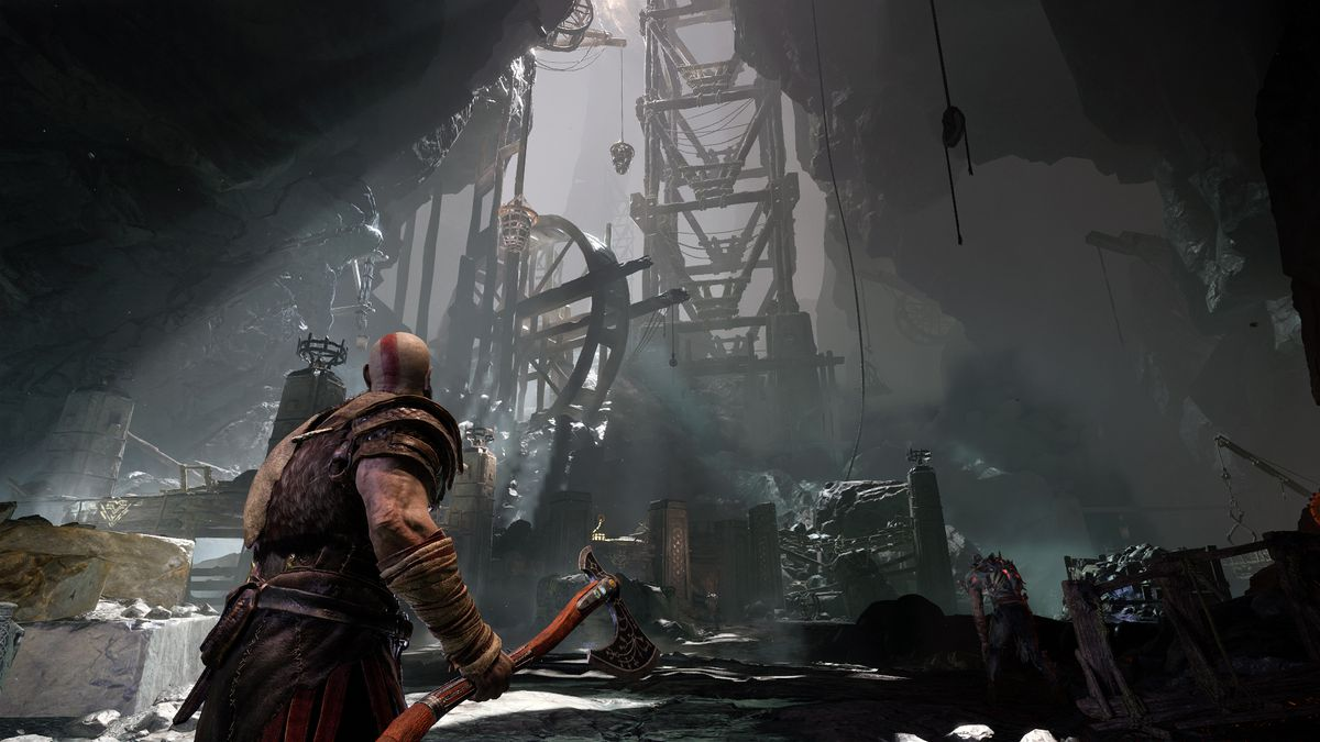 God of War - Kratos looks up at a large wooden contraption in a cave illuminated by a shaft of light
