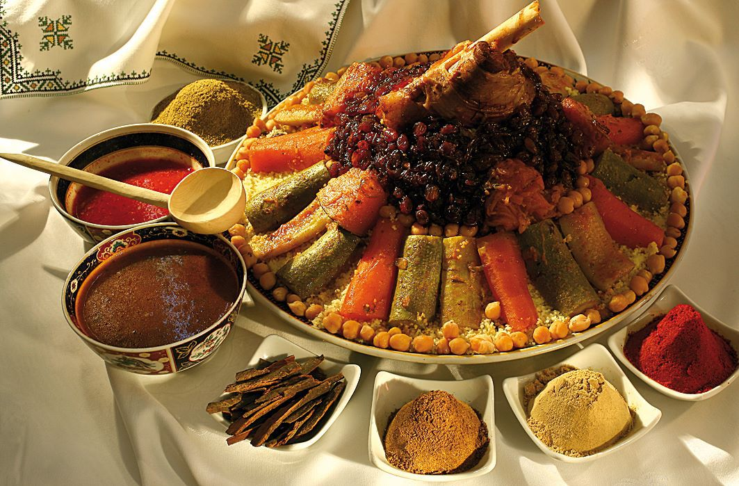 A mound of couscous topped with vegetables, served with an array of sauces and toppings