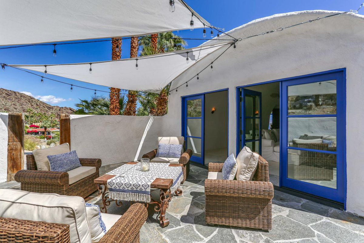 A stone patio has rattan furniture, white shade overhead, and blue doors into the master bedroom.