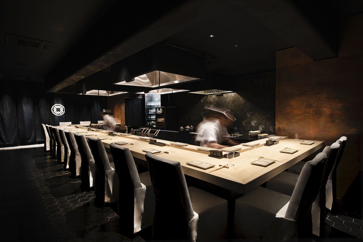A dark restaurant with limited seats, a wooden table with three sides is in the center with chairs all around, and chefs cooking in the kitchen behind it