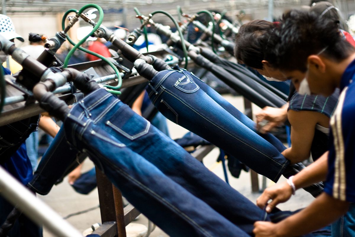Two workers adding finishing touches to jeans in a factory