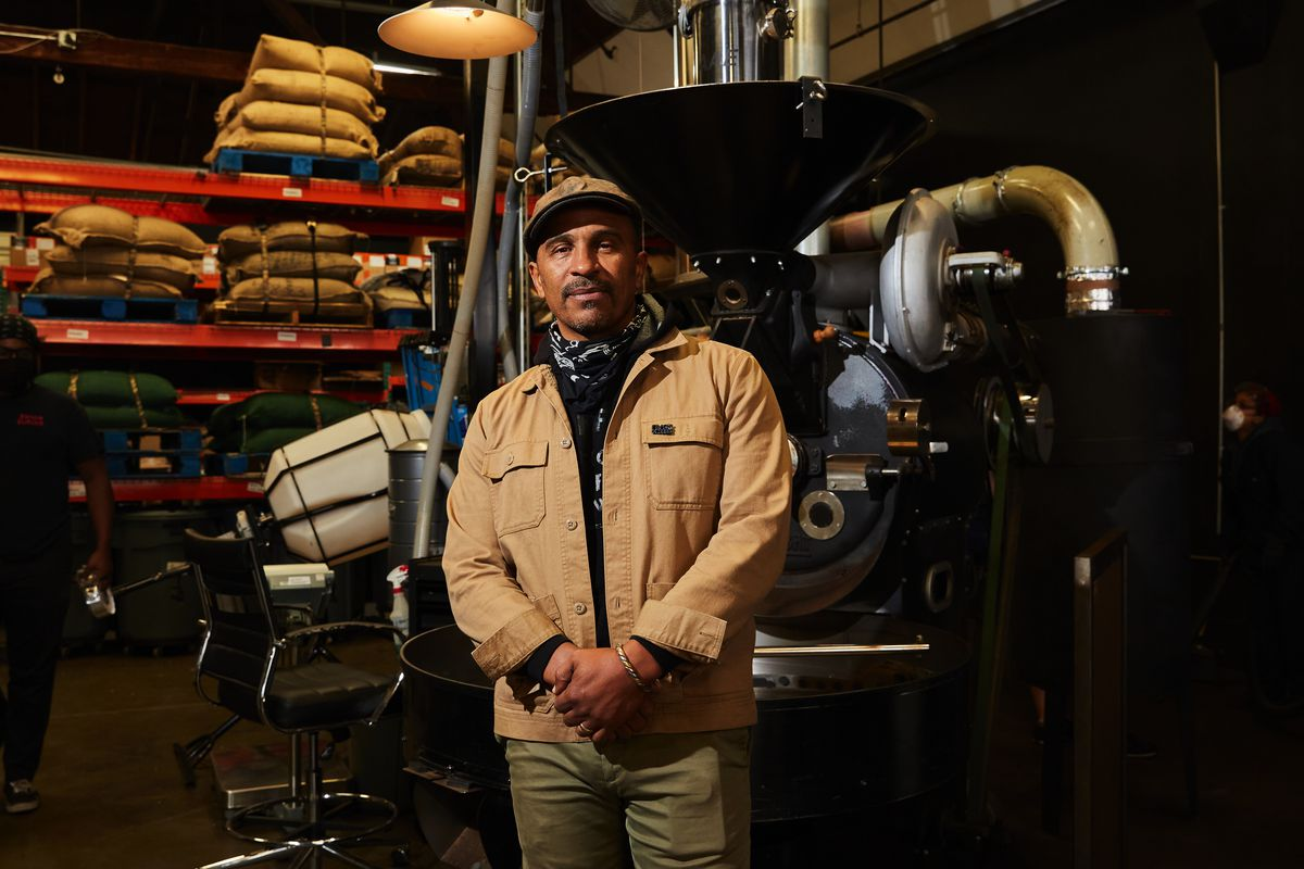 Man wearing cap standing in front of a coffee roaster, with bags of beans stacked on shelves in the background.