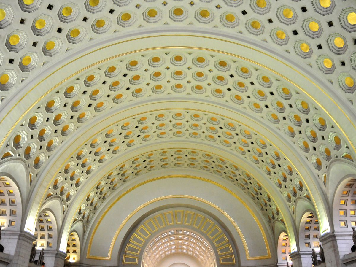 The interior of Union Station in Washington D.C. The ceiling is curved with an elaborate design.