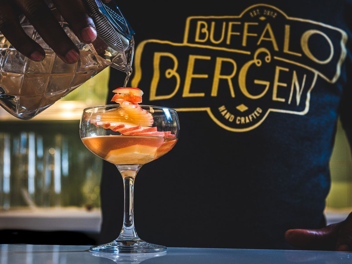 """A """"Vessel-ish"""" cocktail from Buffalo & Bergen comes with scotch, dry vermouth, creole bitters, a touch of honey, and a dramatic spiral of sliced Empire apples."""