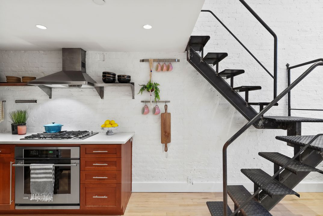 An open kitchen with wooden cabinets and a staircase next to it.