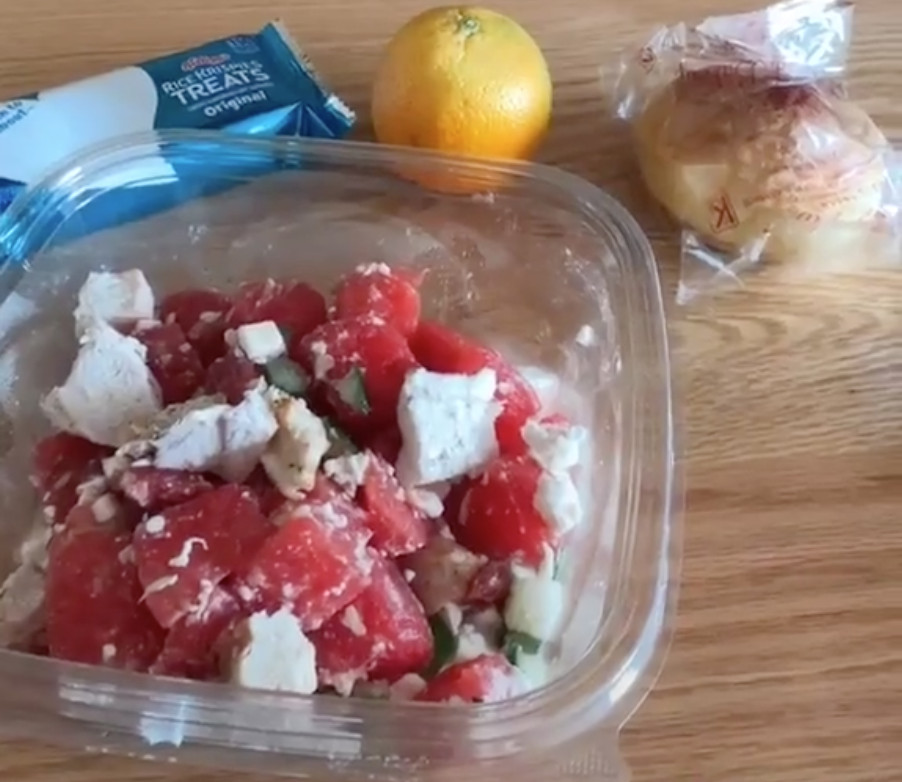 A zoomed in screenshot of watermelon and chicken in a plastic container. A Rice Krispy treat and an orange are visible in the background.