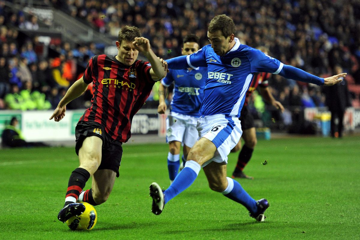 James McArthur of Wigan Athletic challenges James Milner of Manchester City during the Barclays Premier League match between Wigan Athletic and  Manchester City.
