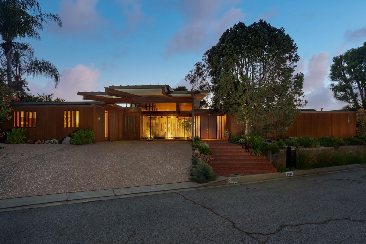 Low-slung house with a driveway and trees.