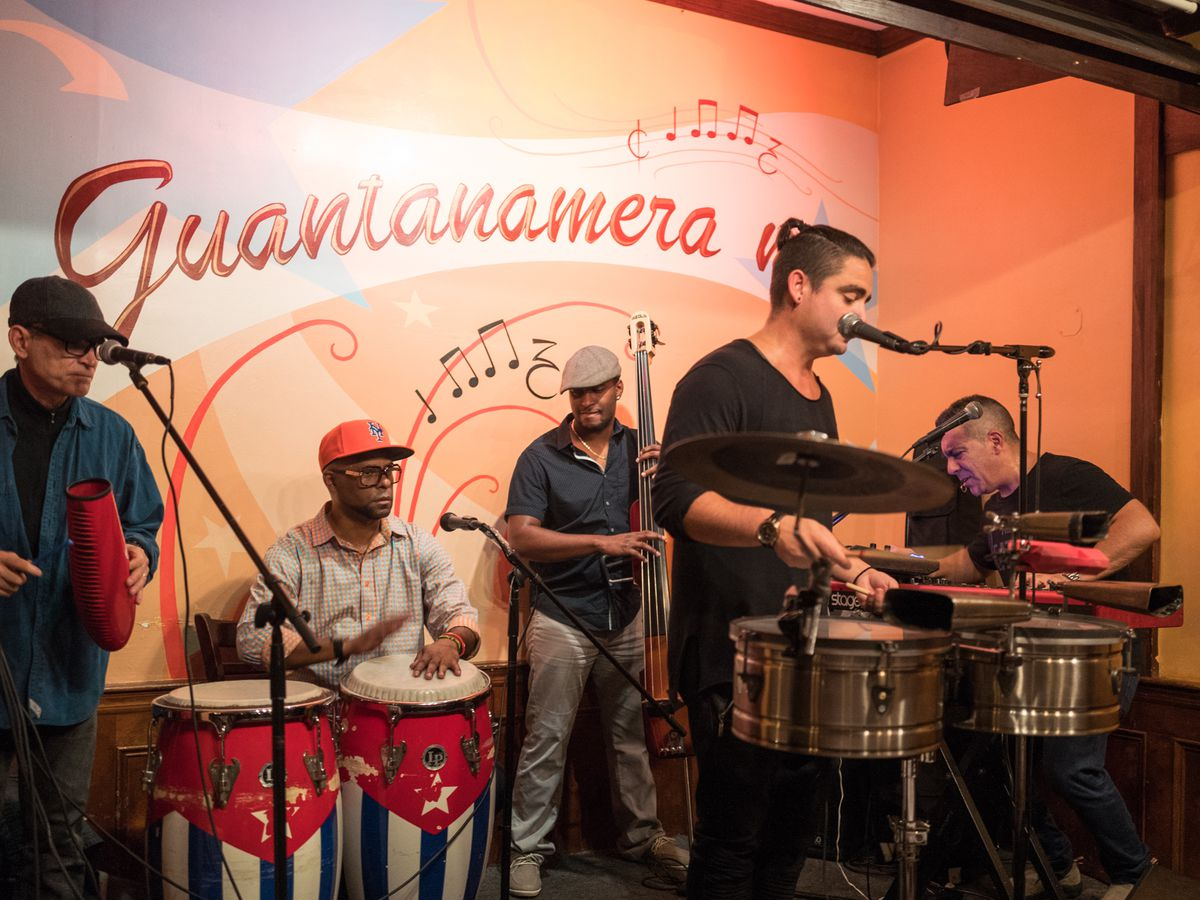 An all-male band plans in front of a mural displaying the word Guantanamera