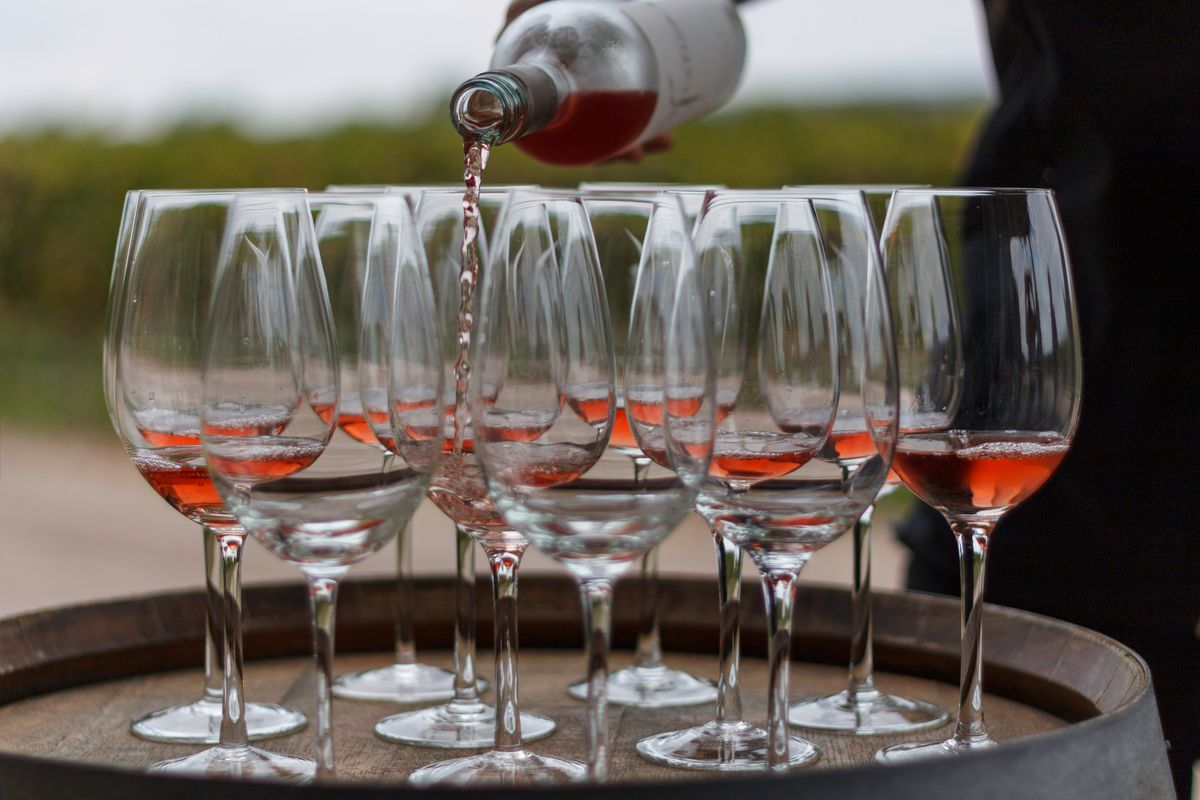 A dozen wine glasses on top of a barrel, as someone pours rose