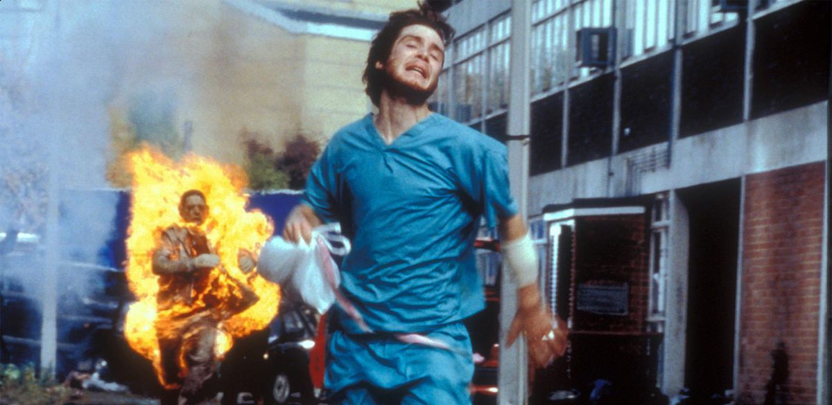 A man in scrubs runs away from a zombie on fire