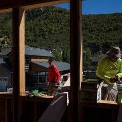 Martin Fragoso Villegas, left, and Raul Peres, right, work on building a zero energy ready home in the Treseder at Little Cottonwood development in Sandy on Friday, Aug. 12, 2016. The development's model home, pictured in background, is featured in the Parade of Homes.