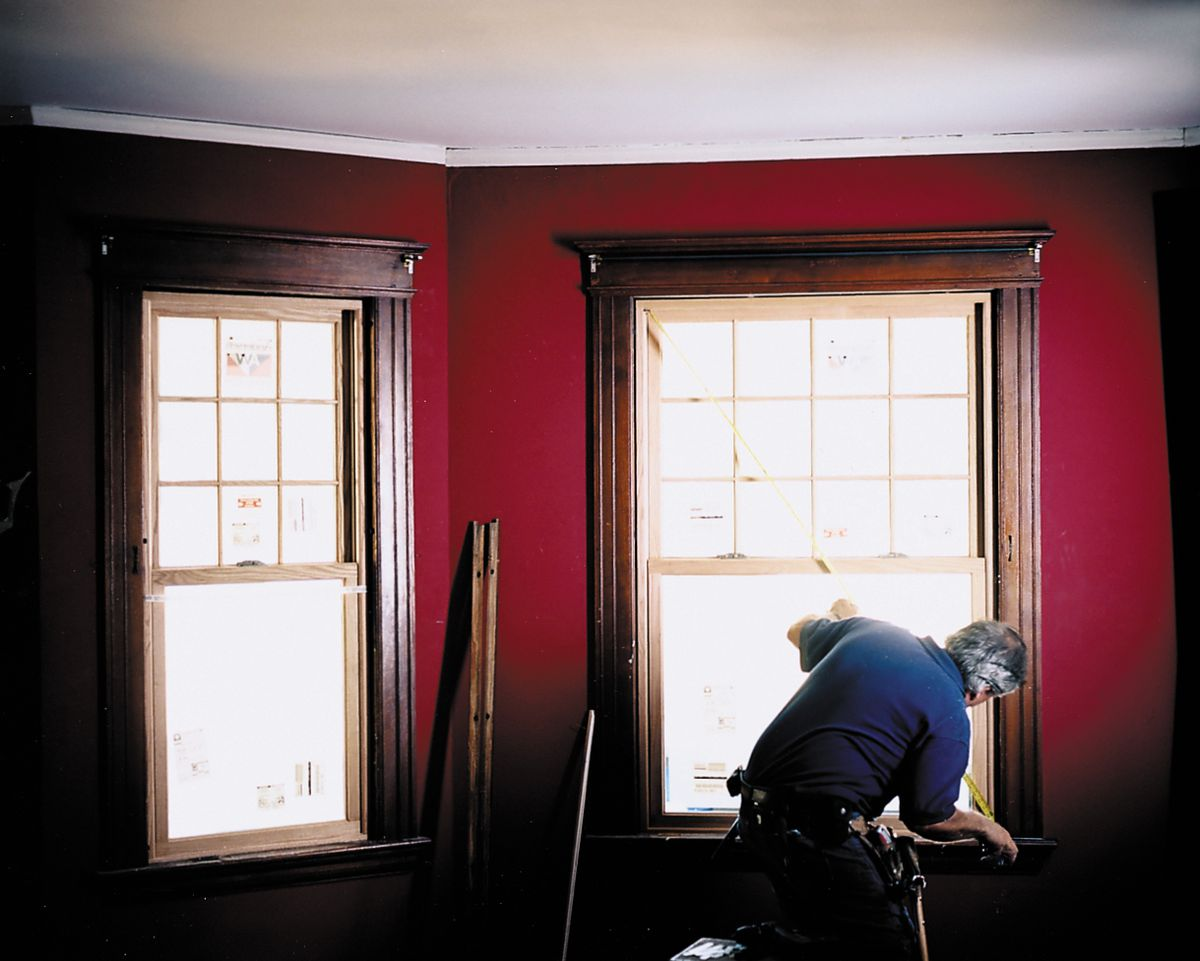 Man Measuring Windows For Replacement