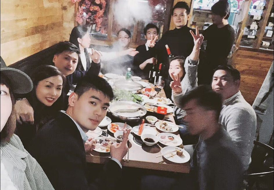 A group of people looking at the camera around the hot pot table.