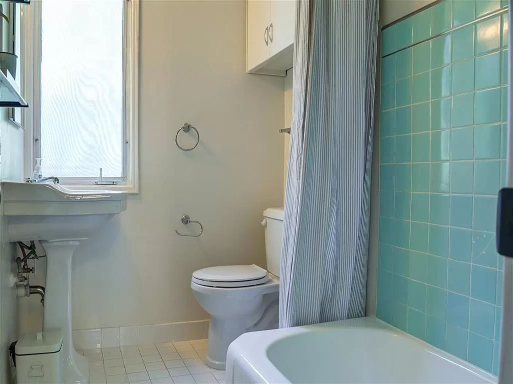 A bathroom with blue-tiled walls and white-tiled floors