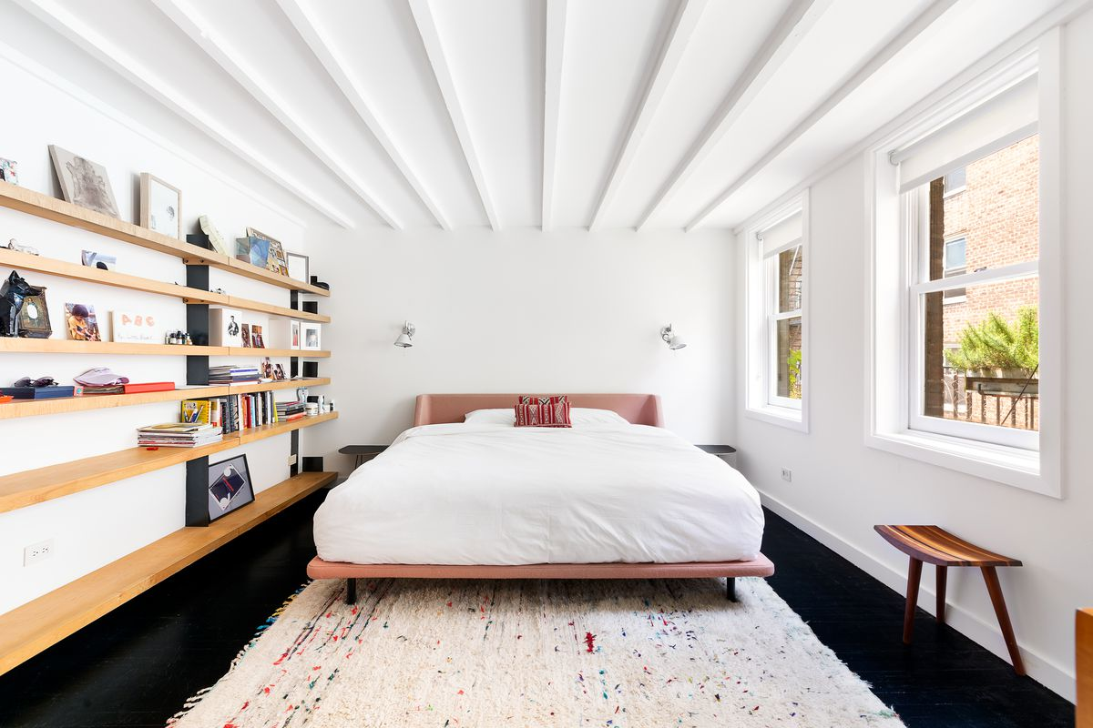 A bedroom with beamed ceilings, two windows, and several wooden shelves.