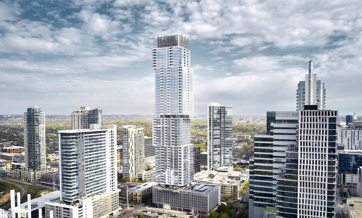 A tall glass building surrounded by shorter buildings. Its structure is like a vertical series of unevenly stacked boxes.