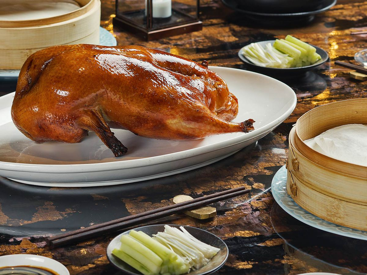 A roasted duck on a white plate with bamboo steamers on either side.