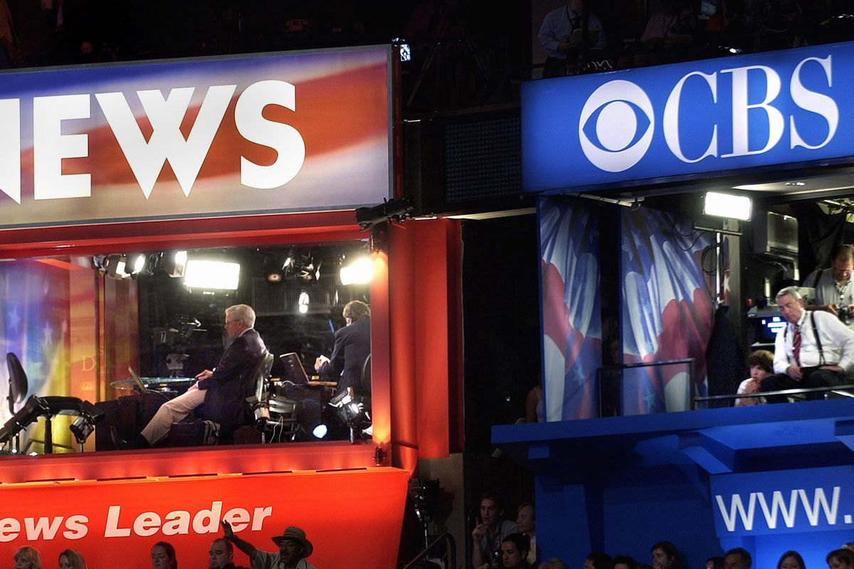 NBC News anchor Tom Brokaw (left) and CBS anchor Dan Rather listen Governor Howard Dean address the Democratic National Convention in Boston, Massachusetts on July 27, 2004.