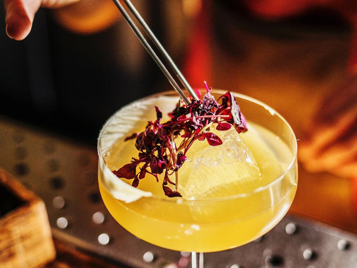 A hand uses tweezers to rest a vibrant bunch of edible flowers on top of a bright cocktail in a coupe glass