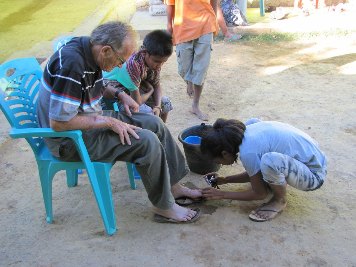 In this 2017 photo provided to The Associated Press, a young girl clips the toenails of now-defrocked Catholic priest Richard Daschbach at the Topu Honis children's shelter in Kutet, East Timor.