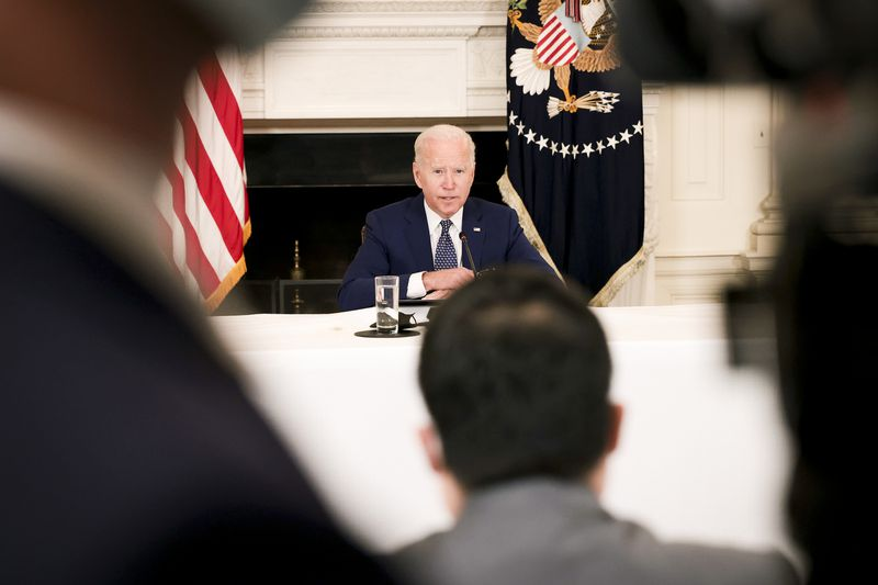President Biden sitting behind a microphone at a conference table.