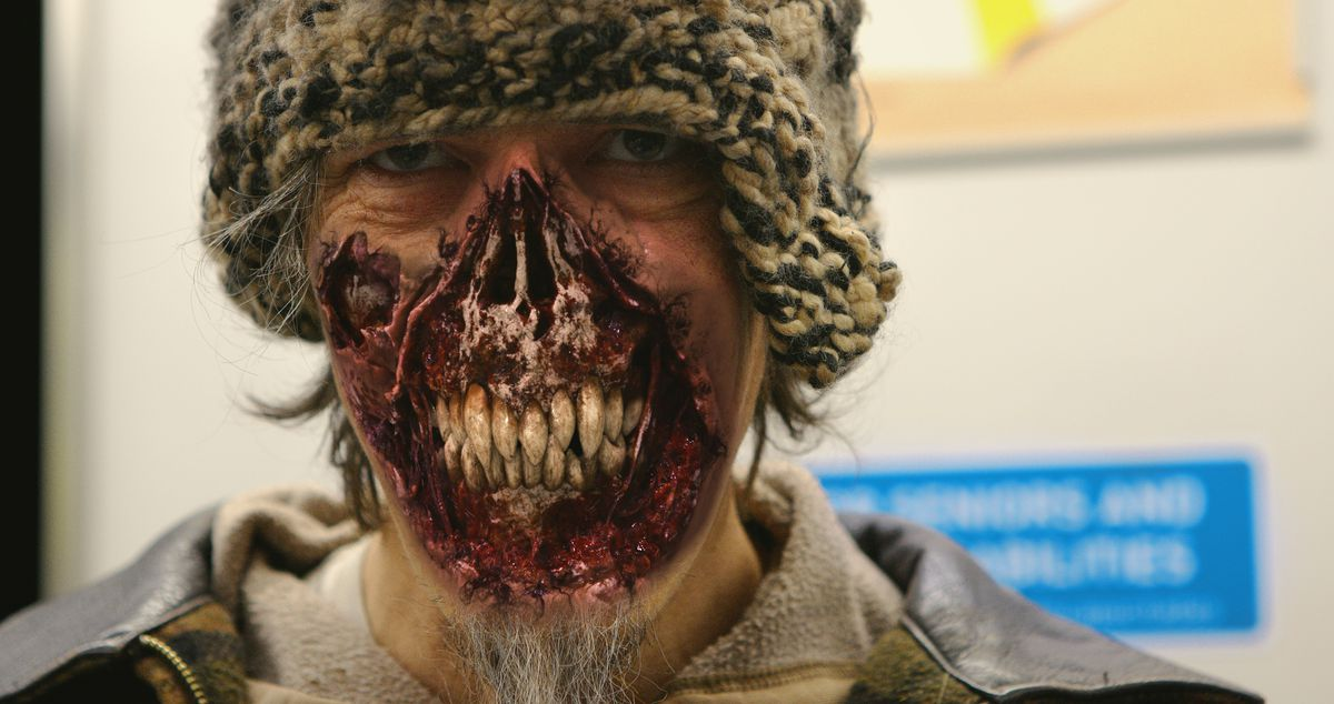 A glowering man in a knit cap, with the skin stripped away from his nose to his chin, exposing bone and snaggle-y teeth