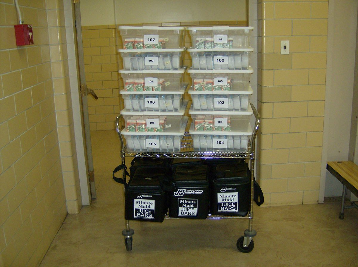 A breakfast cart is loaded with meals, ready for delivery to classrooms in a Denver school.