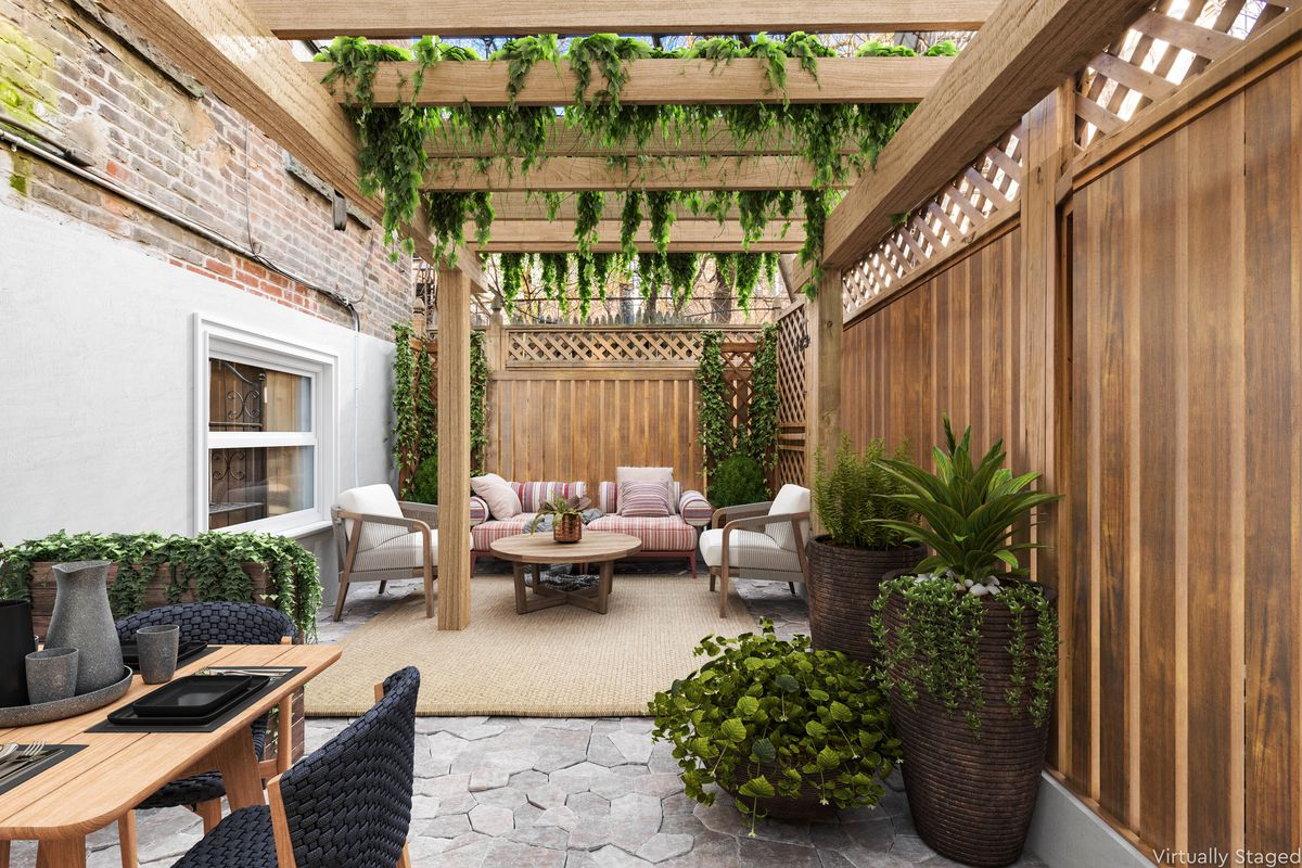 A large patio with brick walls, a wooden fence, several planters, and two seating areas.