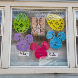 """A sign that reads """"stay safe"""" along with Easter decorations hangs in the window of a home near the corner of North Ashland Avenue and West Julian Street on Monday, April 6, 2020."""