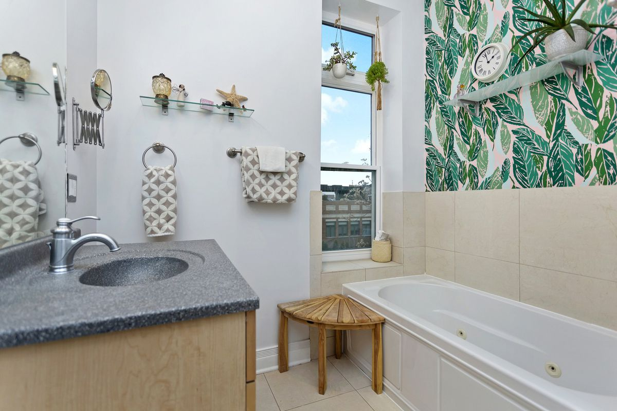 A bathroom with the same wallpaper pattern, a single window, stone vanity, and jacuzzi tub.