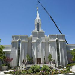 The lightning-damaged Angel Moroni statue atop the Bountiful Utah Temple is replaced on Wednesday, June 1, 2016, in Bountiful. Lightning struck the statue on May 22, 2016.